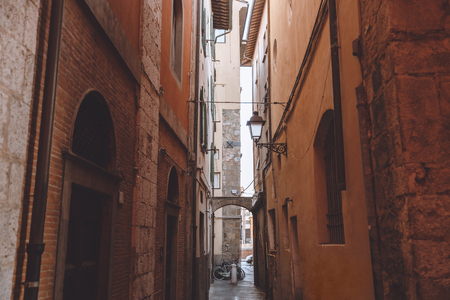 narrow alley between buildings in old city, Pisa, Italy