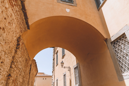 arch between two buildings in old city, Pisa, Italy