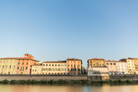 ancient buildings near river in old city with blue sky, Pisa, Italy Stock Photo