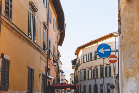 old buildings and road signs on street in Pisa, Italy