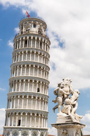 PISA, ITALY - JULY 14, 2017: Leaning tower with flag and sculpture of angels in Pisa, Italy Stock Photo