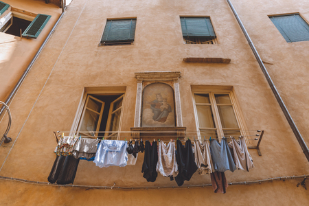 laundry hanging outside buildings with icon on wall in Pisa, Italy
