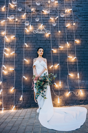 beautiful bride with exotic bouquet under brick wall with light bulbs Stock Photo