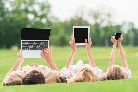 famille couchée sur l'herbe et utilisant des appareils numériques avec des écrans vierges Banque d'images