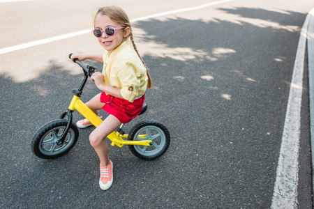 high angle view of cute smiling child in sunglasses riding bicycle Stock Photo