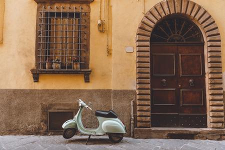 Pisa, Italia - 14 de julio de 2017: scooter vespa de pie cerca del edificio en la ciudad vieja, Pisa, Italia