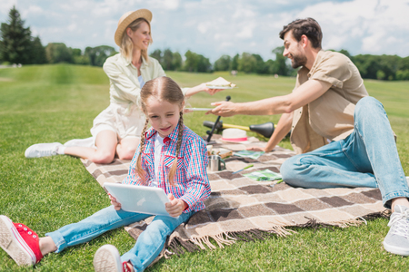 cute little child using digital tablet while resting with parents at picnic Stock Photo
