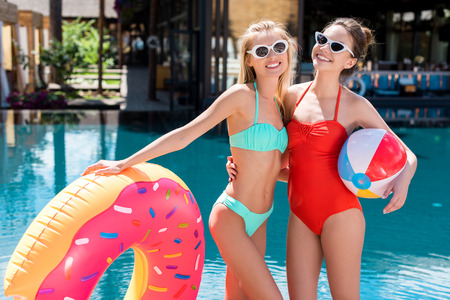 attractive young women with inflatable ring in shape of donut and beach ball standing at poolside Stockfoto