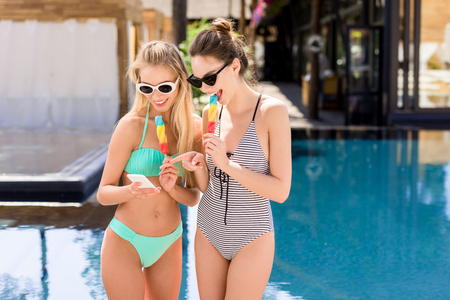 happy young women in swimsuit and bikini eating popsicles and using smartphone at poolside Standard-Bild