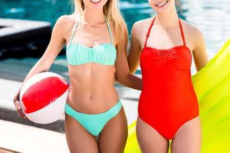 cropped shot of young women with inflatable mattress and beach ball standing at poolside