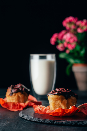 Delicious muffins with glaze and glass of milk on dark background
