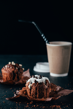 Sweet chocolate muffins with cup of coffee on table
