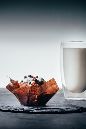Sweet cupcake with chocolate chips and glass of milk on slate board 版權商用圖片