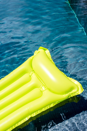 close-up shot of green inflatable mattress floating in swimming pool