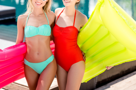 cropped shot of smiling young women with inflatable mattresses standing at poolside