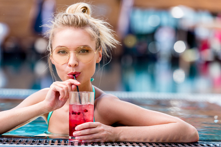beautiful young woman drinking fresh cocktail at poolside
