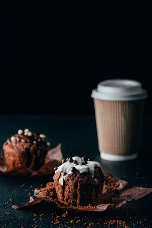 Delicious muffins with glaze with cup of coffee on table