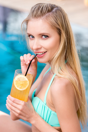 beautiful young woman with refreshing orange beverage looking at camera at poolside Stok Fotoğraf
