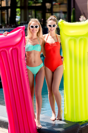 attractive young women with inflatable mattresses standing at poolside and looking at camera