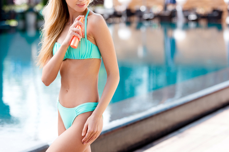 cropped shot of young woman applying sunscreen at poolside Foto de archivo