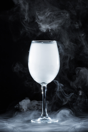 wineglass with white smoke on black background