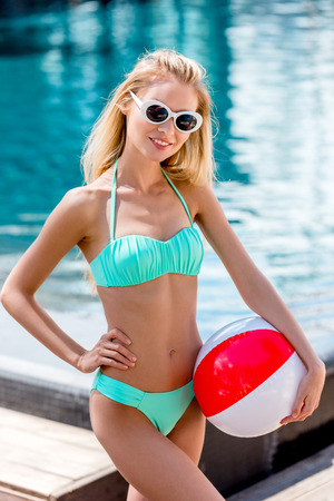 attractive young woman with beach ball at poolside