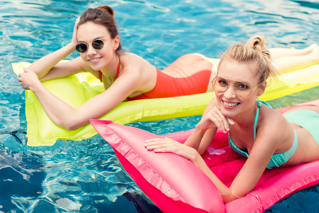 happy young women lying on inflatable mattresses in swimming pool and looking at camera 免版税图像 - 105913019