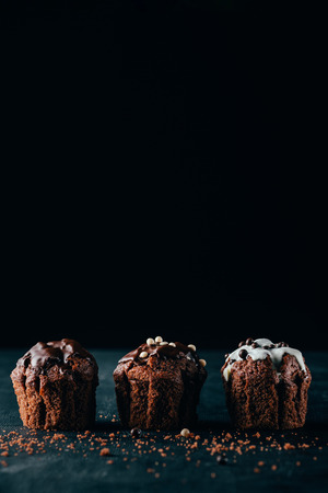 Delicious muffins with glaze on dark background 版權商用圖片