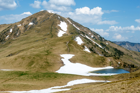 mountain covered by snow and lake under cloudy blue sky in Romania