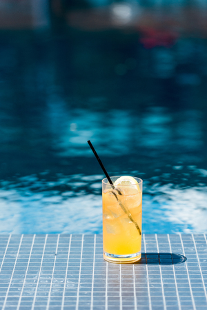 close-up shot of glass of delicious orange cocktail on poolside