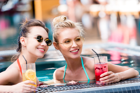 beautiful young women with delicious cocktails relaxing in swimming pool and chatting