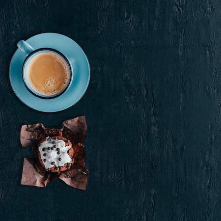 Sweet chocolate muffin and cup of coffee on wooden background