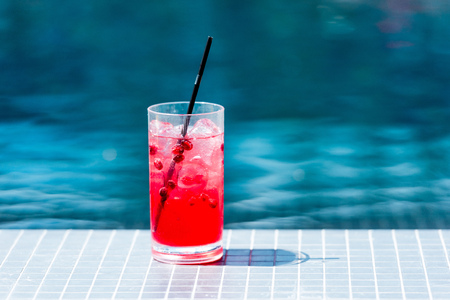 close-up shot of glass of red berry cocktail on poolside