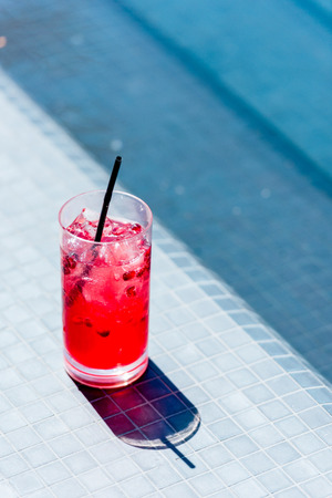 close-up shot of glass of berry cocktail on poolside