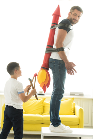 disobedient son playing with tied father with rocket toy on back at home
