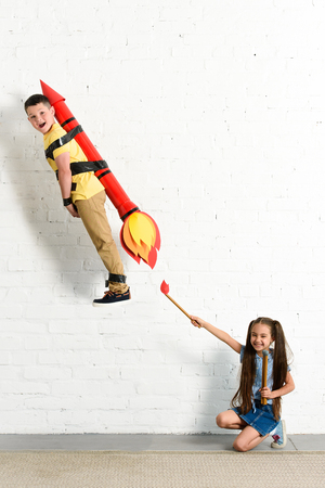 happy sister pretending setting on fire toy rocket with brother at home Banco de Imagens