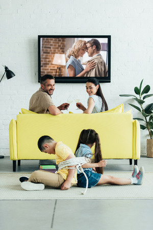 happy parents resting with champagne and children sitting tied with rope on floor at home Stock Photo
