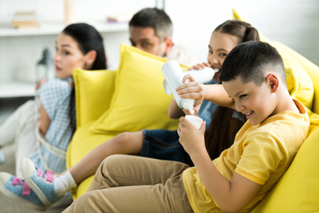 tied parents sitting near sofa and children eating sweets at home, parenthood concept