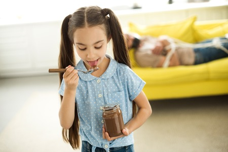 father lying tied on sofa and daughter eating chocolate at home Banco de Imagens