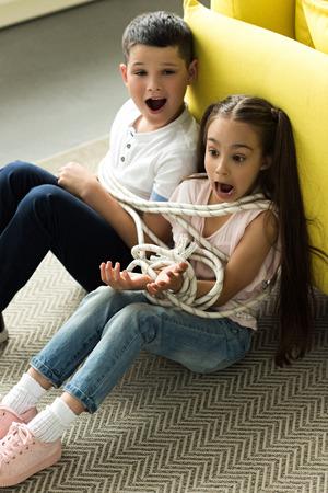 gefesselt mit Seil Schwester und Bruder sitzen auf dem Boden und schreien zu Hause