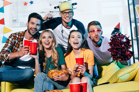 happy young male and female friends drinking beer and eating snack at home party Stock Photo