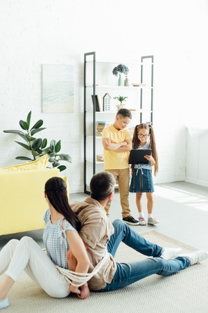 parents sitting tied with rope on floor and children holding clipboard at home