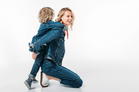 side view of happy mother giving piggyback to son on white
