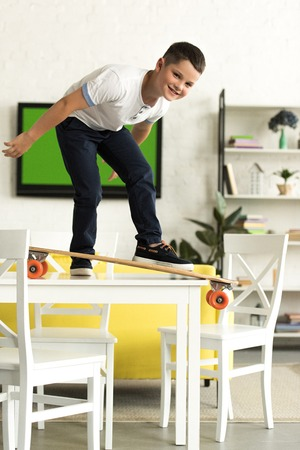 pre-adolescent boy standing on skateboard on table at home and looking at camera