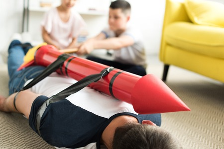 tied father with rocket toy lying on floor and children playing with him, parenthood concept