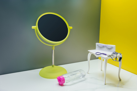 makeup mirror and dressing table with bottle of lotion and eyelash curler in miniature room