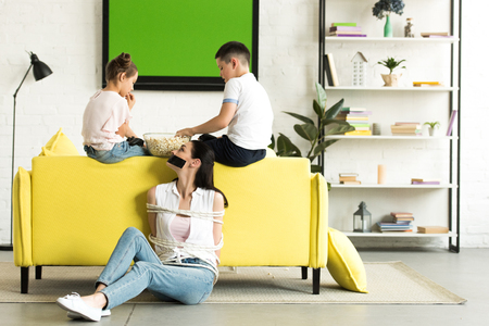 side view of children eating popcorn and mother sitting tied with rope on floor at home Foto de archivo