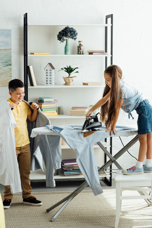 sister and brother ironing clothes at home
