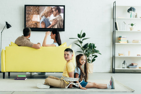parents watching movie and children sitting tied with rope on floor at home Foto de archivo