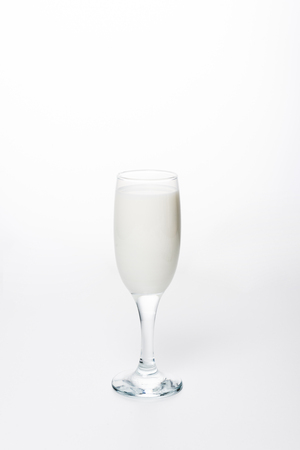 close-up shot of fresh milk in wineglass on white surface